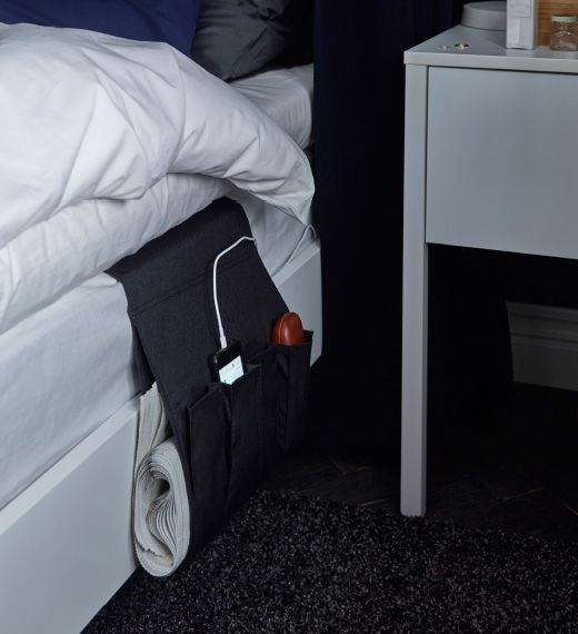 A remote control storage pocket has been remodelled to store a charging mobile phone while hanging from the side of a bed.