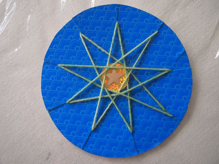 Nine-Pointed Stars- Piggybacking on another pin, I adapted it to make 9 points. We made a colorful backing by gluing origami paper onto cereal box cardboard and cutting out a circle with 9 slits. Working counter-clockwise, string goes through every 4th slit.