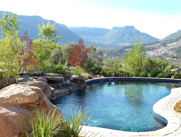 Rock sculpture and waterfalls on freeform swimming pool.