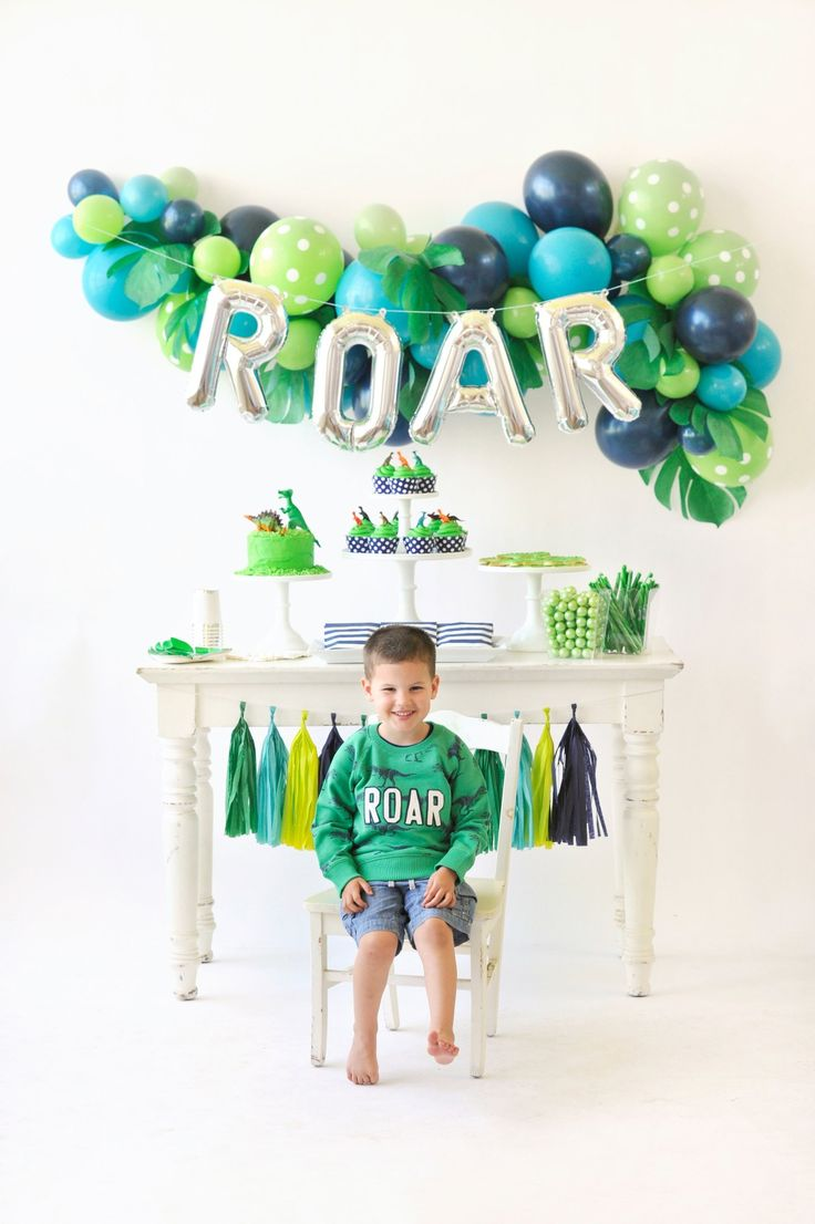 """Welcome to the dinosaur jungle! Children's birthday party inspiration. Dessert table decor. Blue and green balloons. Tassel garland. Little boy in """"roar"""" party sweatshirt. T-Rex/Dinosaur Partystyling by Happy Wish Company. Photography by Tammy Hughes Photography. Stationery by Minted artist, Patricia Wallace."""