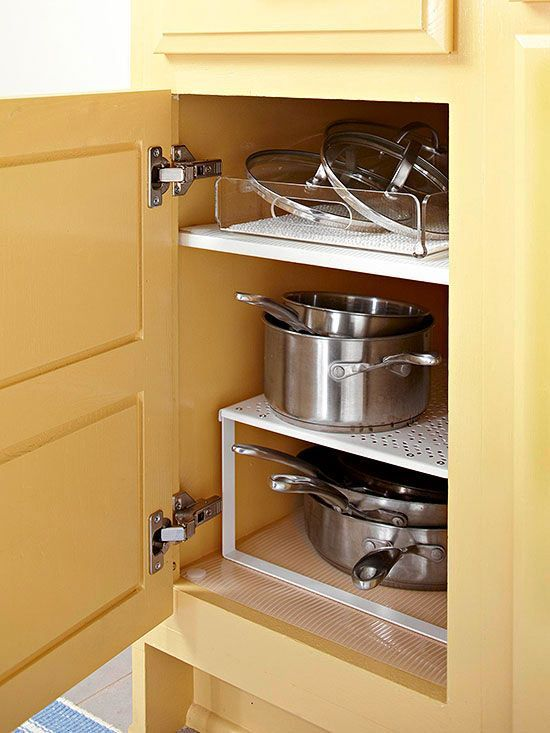 Most kitchen cabinets include one shelf, and it alone is often not enough. Add a second tiered shelf to bring order to pots, pans, skillets, and lids. Organizing all lids together allows pots to rest inside each other and gives you an opportunity to use another storage container for lids.