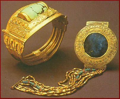 *KING TUTANKHAMUN: 2 of the bracelets found on Tatankhamun's arms. The massive rigid hinged gold example (a) has a cylinder of turquoise inset into a plaque smothered w/ applied wire + granulation. The other ()b) has a flexible strap of gold + glass beads attached to the circular gold plaque, also highly decorated, w/ a central lapis lazuli inset. From the tomb of Tutankhamun, Valley of the Kings, W. Thebes, 18th Dynasty 13345-1325 B.C.