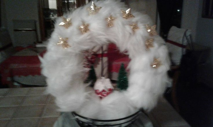 White faux fur wreath  With a small house and trees  All items are clued to the fur Golden stars is also glued  The wreath is very different because of the fur