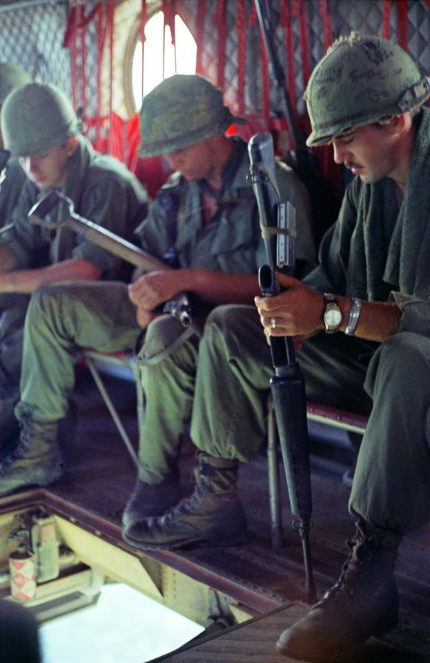 Soldiers aboard an airborne Chinook with a bird's-eye view through the helicopter's cargo sling door. Note the commonly-seen method of how the soldiers have tied the laces of their jungle boots, as well as the helmet band securing the 20rnd magazine to the first man's M16.