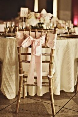 Sedie dorate per il ricevimento con fiocco rosa e cuscino bianco