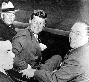"Oct 1959: JFK courting Chicago Mayor Richard J. Daley at Comiskey Park during Dodgers-White Sox World Series game, along with  baseball commissioner  ""Happy"" Chandler (with hat) and Daley's son, Richard M., then a state senator, in foreground. Chicago Sun-Times."