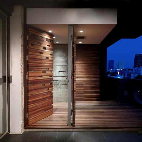 Thai architects Architectkidd built an outdoor shower room behind wooden screens on the balcony of this renovated apartment in Bangkok