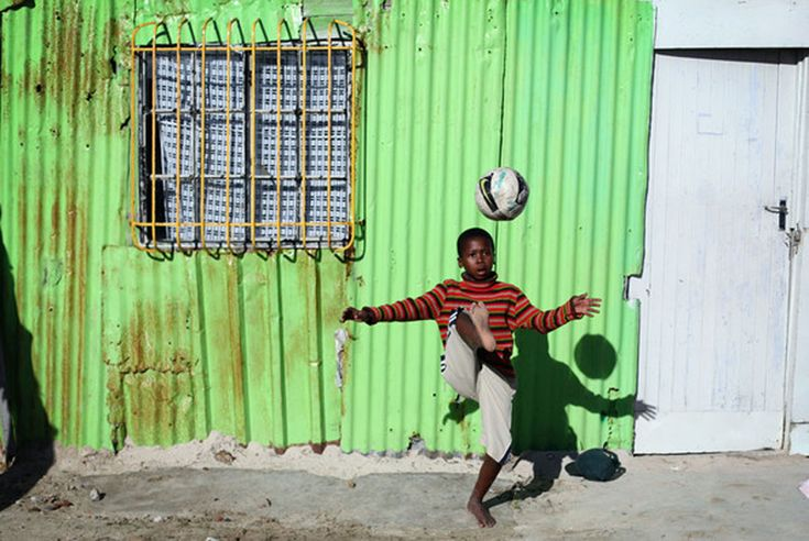 A young boy playing soccer in the township. It is a sport also very popular in South Africa.