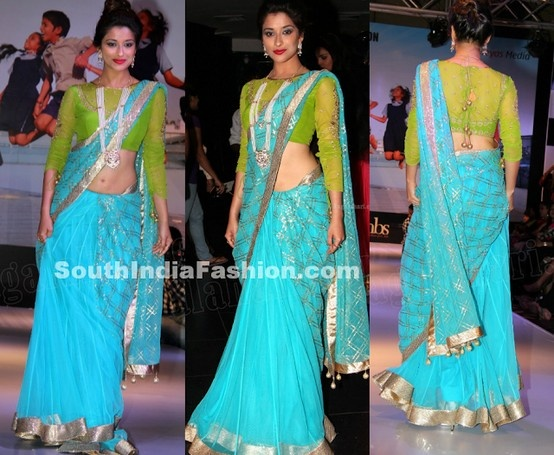 South indian actress Madhurima in blue half and half net saree, paired up with designer netted blouse with quarter sleeves.