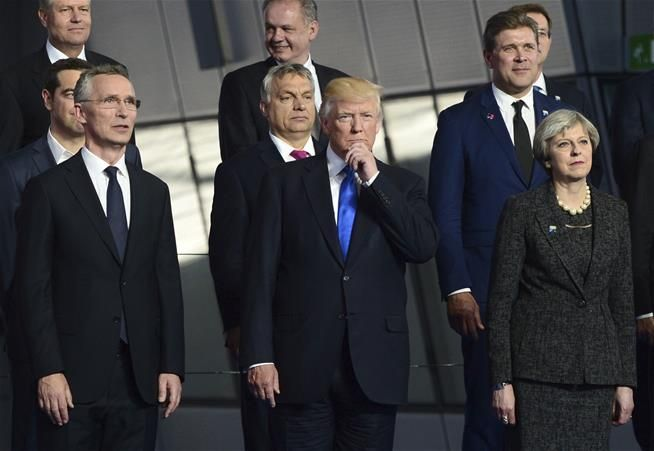 President Trump, flanked by British Prime Minister Theresa May, right, and NATO Secretary General Jens Stoltenberg, joins fellow leaders in a group photo at NATO headquarters