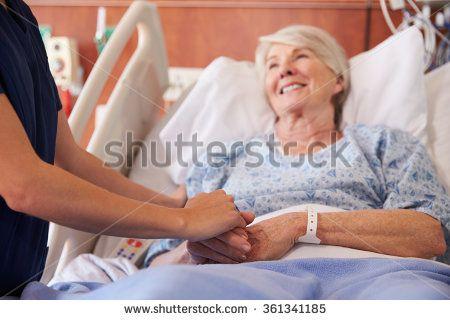 Close Up Of Hospital Nurse Holding Senior Patient's Hand - stock photo