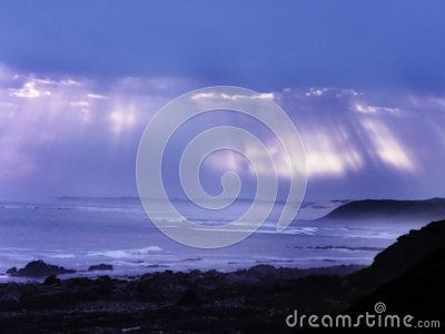 A view of shafts of sunlight showing through the clouds over the ocean.