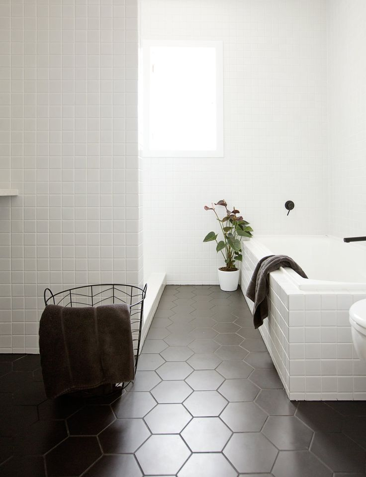Matte black tile with black grout gives an all white bathroom an elegant look! We are loving this new trend.