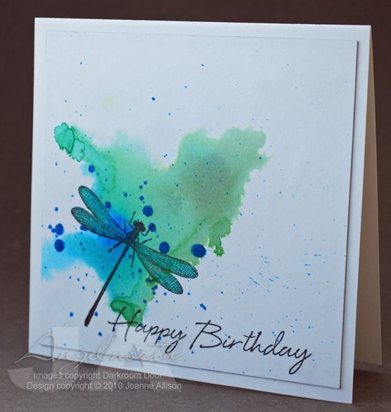 By Joanne Allison (Angelnorth at Splitcoaststampers). Inks dripped onto wet surface so they run & pool. She used Distress reindeers Salty Ocean, Mowed Grass, Bundled Sage. Dragonfly stamped in VersaFine Onyx Black with turquoise & green glitter pens used on the wings.