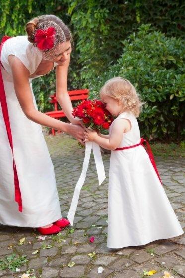 Blumenkinderkleid mit leicht ausgestelltem Rock, passend zum Brautkleid.    Die Taille wird von einem schmalen, roten Band geziert, welches im Rücken