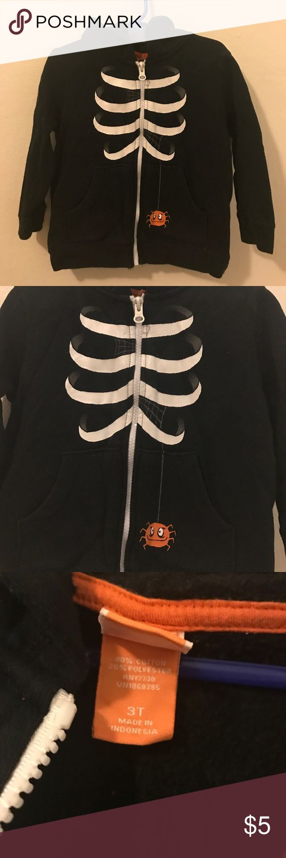 Skeleton and spider zip up Halloween hoodie Size 3T black hoodie with a white zipper, with a fun little rib cage of a skeleton and a little orange spider hanging out on the the left pocket. Everything in awesome condition. No pulls, or issues. Please ask questions if you have them! 🖤 Target Shirts & Tops Sweatshirts & Hoodies