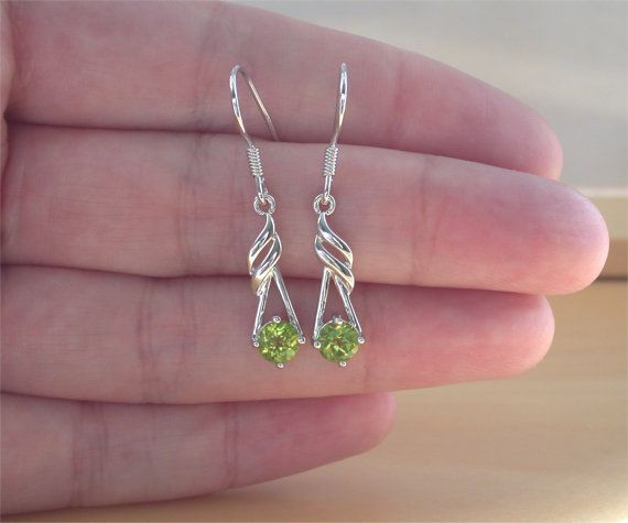 Stunning pair of sterling silver, flame design earrings sret with genuine peridot gemstones. Each earring measures 20mm length x 7mm width.