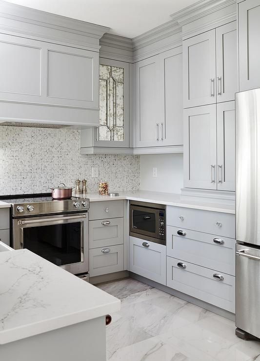 Small gray u-shaped kitchen clad in polished marble floor tiles boasts stacked gray shaker cabinet fixed above gray shaker lower cabinets accented with polished nickel hardware, an under counter microwave, and a white quartz countertop.