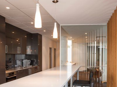 Concept Office Interiors designed this kitchen area to be modern with warm lighting and clean lines.