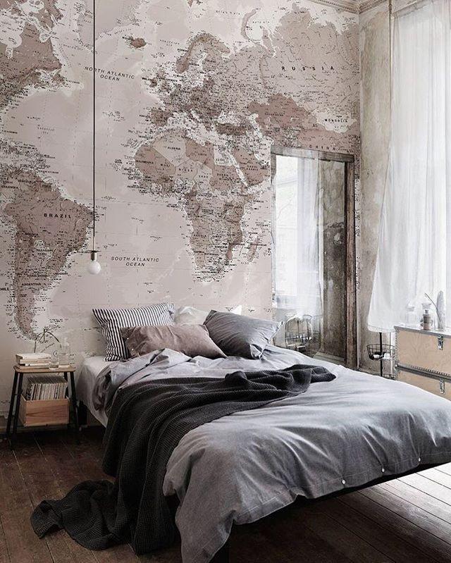 Carta da parati con mappa per parete dietro letto. Toni neutri.