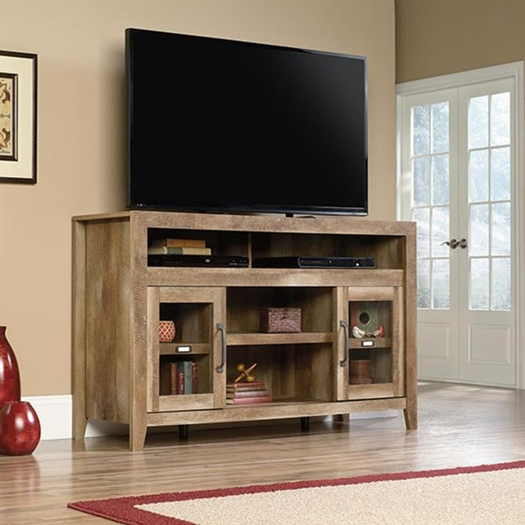 """The Dakota 60"""" TV Stand from Sauder Woodworking Co. comes in a sandy brown craftsman oak finish. Features 6 shelves with adjustable shelves behind safety-tempered glass doors and enclosed back cord access. Perfect for storage, display, and electronics. Maximum weight: 95 pounds. Maximum TV size: 60 inches. Sauder Dakota Pass Rustic Storage 60"""" TV Stand 
