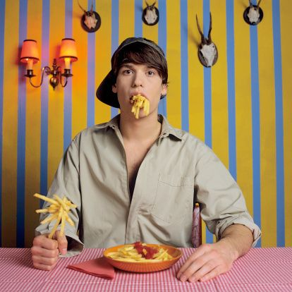 Stock Photo : Young man eating french fries
