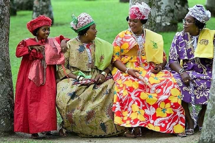 Vrouwen gekleed in typische Surinaamse kleding voor feesten ...
