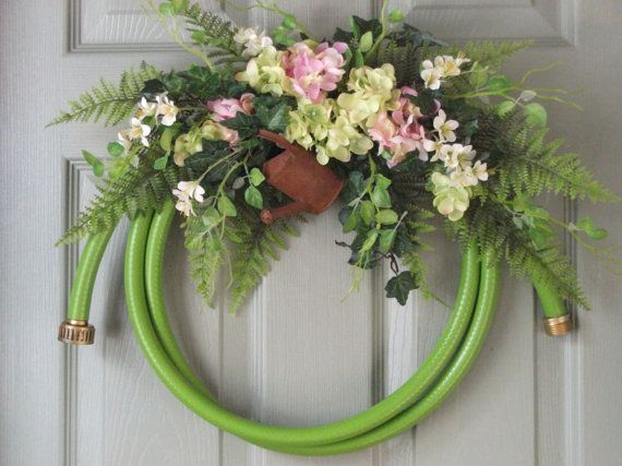 Country Garden hose wreath decorated with artificial flowers.  A very way to welcome friends and neighbors!