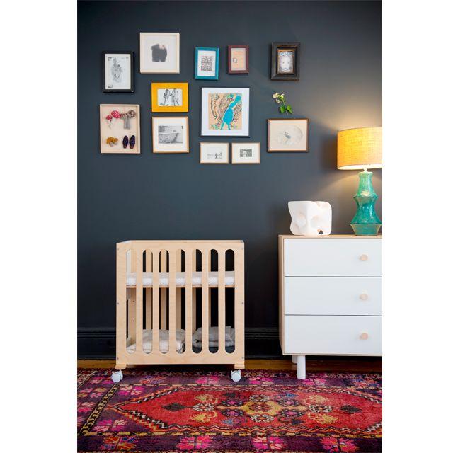 Oeuf Fawn Bassinet and Oeuf Fawn Merlin Dresser in a dark blue nursery with photo collage and Persian rug. | #oeuf #ellaandelliot | ella+elliot | Canada | Vancouver | Toronto | Image via @ellaandelliot Instagram