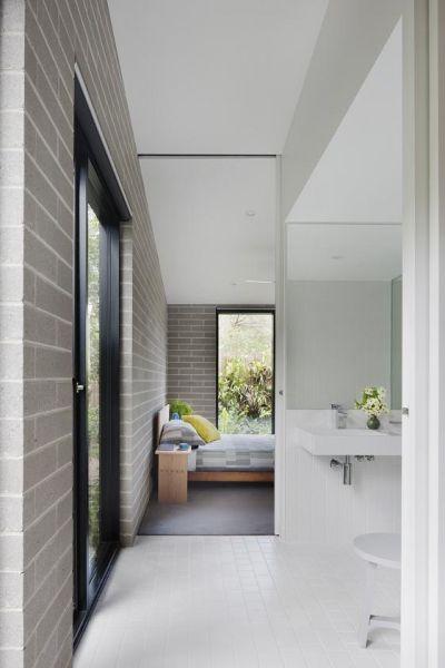 Una delle due camere da letto della Hover House, preceduta da un piccolo bagno privato con pavimento di piastrelle bianche. La zona notte è invece definita dalla texture del cemento