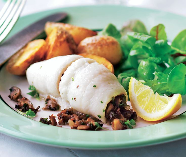 White plaice stuffed with mushrooms and served with potatoes and green leaves