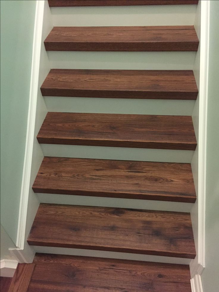 Laminate seamlessly installed on steps, with stained cap at front. Custom project by Grand Floors. **laminate installed on steps in recommended if both sides are closed.