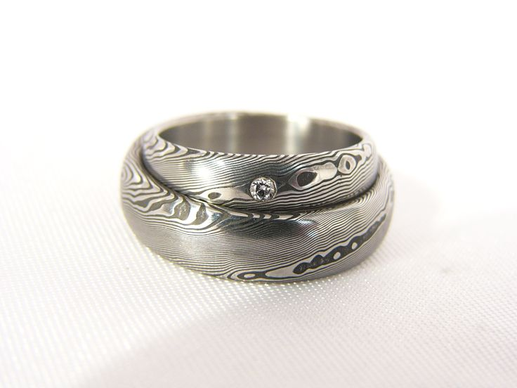 Pár snubních prstenů Ruberdur z damascénské oceli Do detailu zpracované šperky z damascénské oceli, varianta s diamantem. V nabídce též varianta bez kamene či s kamenem dle volby zákazníka. Velikost diamantu je , vzor eyes, hluboký lept. Diamant vždy s certifikátem pravosti.