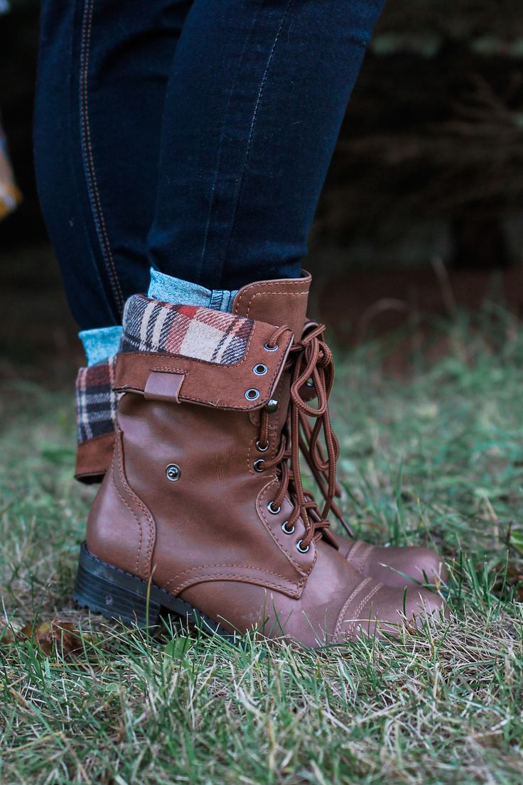 Command some serious attention in these leatherette combat boots, featuring a fold over shaft with plaid lining. Lace-up front. Round toe. Tonal topstitching. Stacked low heel. Rugged outsole. Heel he