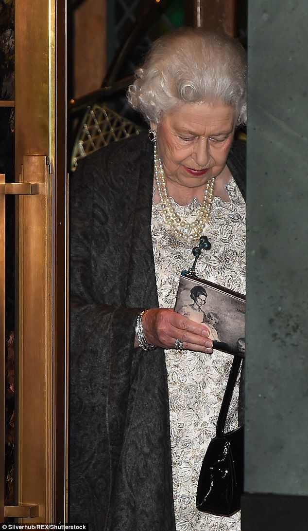 The Queen was seen brandishing a bespoke purse as she left The Ivy restaurant in London last night, personalised with an image of a woman with two children
