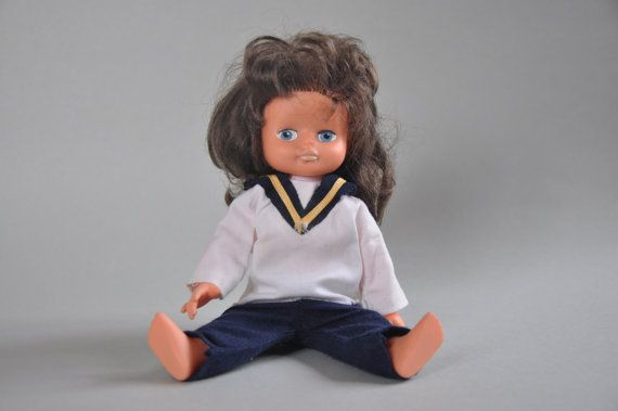 This absolutely adorable vintage doll is dressed in the sailor costume. She has blue eyes and dark curly hair, face is hand painted, soft plastic