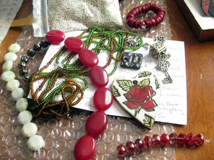 ... and the beads!  The heart shaped rose pendant & rectangular link are from Earthenwood Studios, and she also sent a variety of Czech beads, charms, red Malay jade, deep red wood? beads (not sure, but they are lovely & earthy), and seed beads!!  This will be so much fun to work with, I am already inspired :)