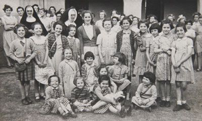 """Group portrait of nuns with young girls. Child migrants on arrival at Nazareth House in Geraldton 1953 – Yvonne standing third from left. Lent by Yvonne Radzevicius    """"My lasting thought of Great Britain was being herded like cattle to board the New Australia. The nuns told me my parents were dead and I had no brothers or sisters."""""""