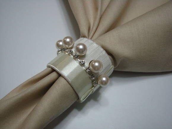 Porta - guardanapo confeccionado com estrutura plástica revestida de fita de cetim, com aplique de pérolas e strass. R$ 8,50