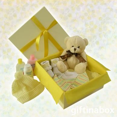 """Beautiful selection of baby essentials to pamper baby in every way. All goods are lovingly presented in a cream gift hamper box decorated with ribbons and tissue paper. This gift can be made up in blue (baby boy) or pink (baby girl). Please advise under """"Special Instructions""""   Cuddly teddy bear Sock booties 2 cotton vests Baby soap Baby powder Baby shampoo Baby beanie"""