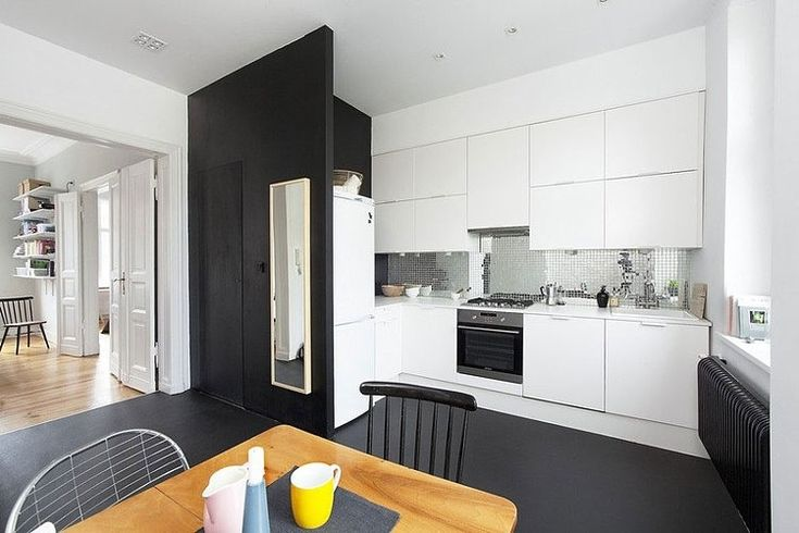 Black floors, white kitchen, pop of yellow.  Poznan Apartment by Halo. Architekci