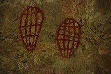 "Ngaro Cave Painting, ""Public park with boardwalk into mouth of a cave in Nara Inlet on Hook Island in the Whitsunday National Forest, Queensland, Australia. The painting is by the Ngaro aboriginal people and is thousands of years old. The painting's symbolism or figurative subject is unknown but resembles a Pandanas fruit that the Ngaro people are known to have used for food. It also resembles the inside of a sea turtle shell, which was also a common staple of the Ngaro people."""