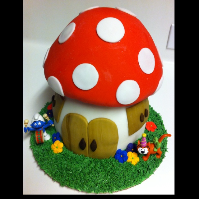 """Smurf cake: This took a lot of time but wasn't difficult. I used two stacked 8"""" cakes for the bottom, carved down a bit; and the doll cake pan for the top. I dyed my own fondant and used it like clay. I piped the grass and added smurfs. Easy peasy! ;-)"""