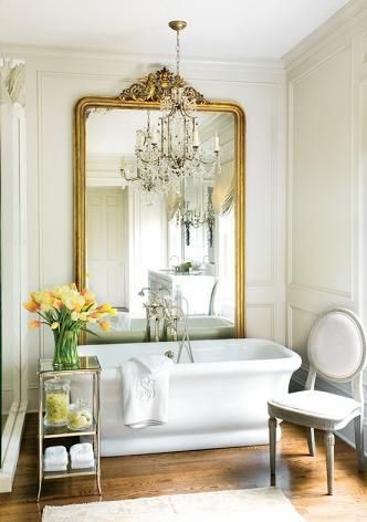 Elements Of A French Country Bathroom Design. Love the mirror behind the tub, and the chandelier.