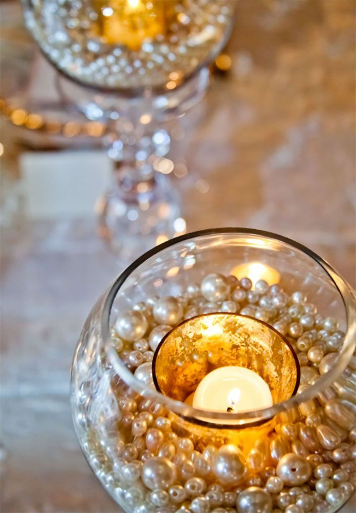 Glass candle holders with votive holder and candle surrounded by pearls.