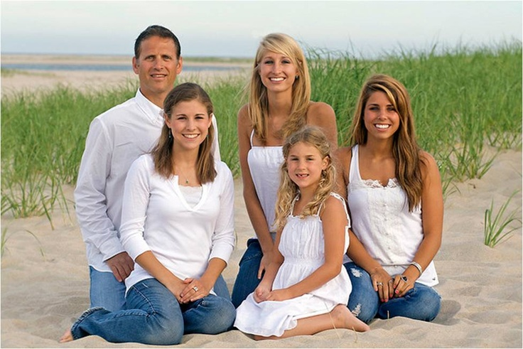 Pose family sitting at the beach wearing jeans and white linen shirts