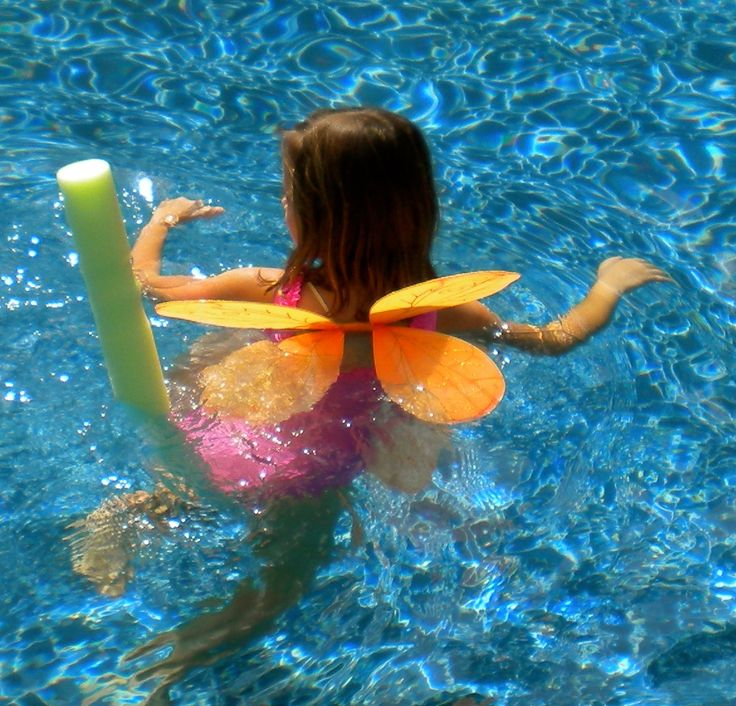 Kids pool party games for a fairy themed party using wings and foam noodles.