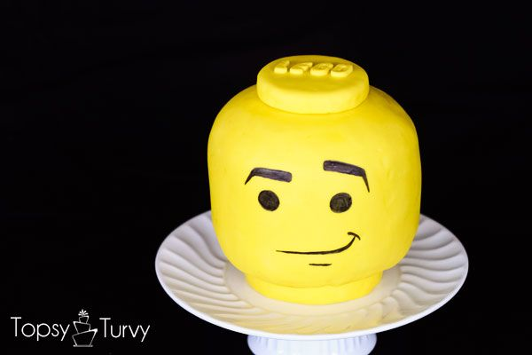 a tutorial for making your own carved lego head fondant covered cake for any lego themed celebration. personalize the expression of your lego head with edible markers