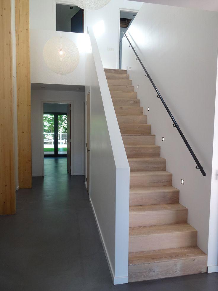 Deze houten trap in combinatie met een zwart stalen trapleuning, wit stucwerk en een grijze gietvloer zorgt voor een modern maar warm geheel.