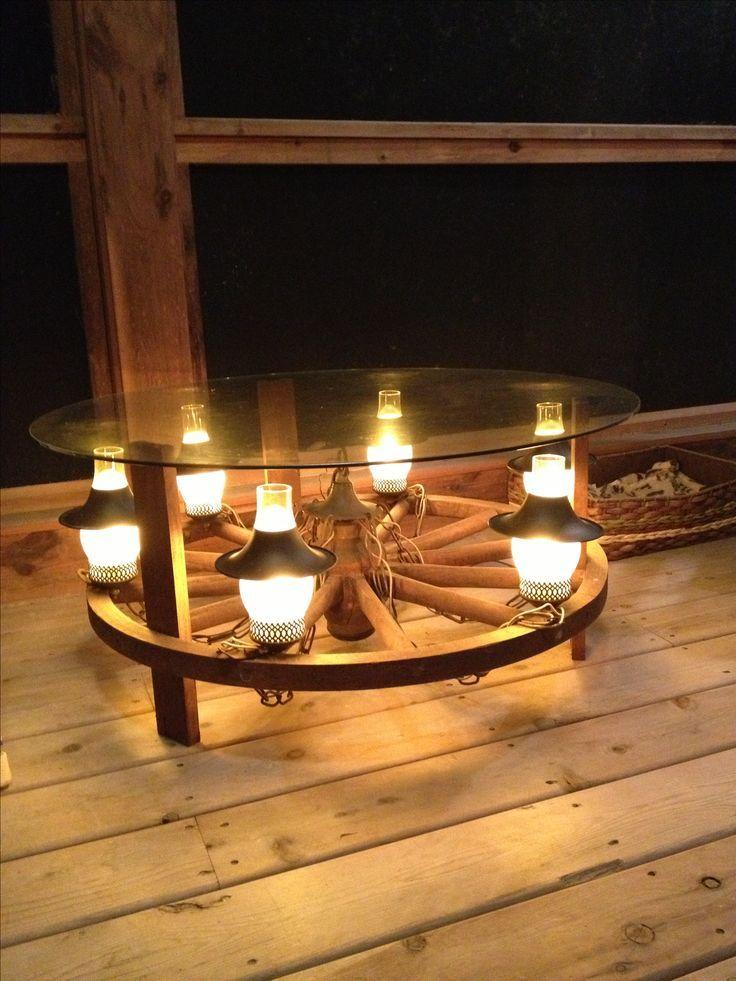 Was für eine kreative Idee! Ein Couchtisch aus einem Wagenrad Kronleuchter! Fügen Sie drei Holzbeine und eine Glasplatte hinzu und es wird zum perfekten beleuchteten Accessoire und Gesprächsteil, um Ihre Veranda zu dekorieren.